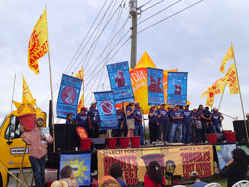 CIW members hold signs that demand the