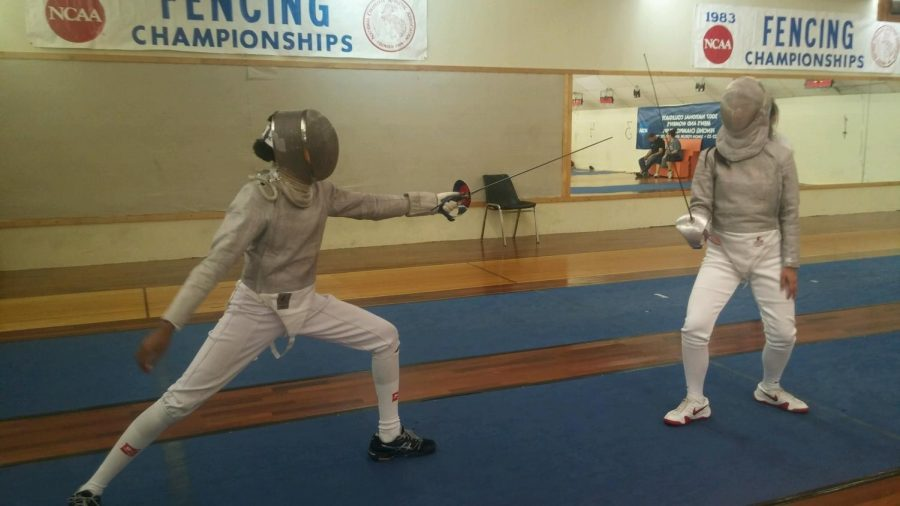 Junior Kristen Palmer (left) fences against her friend, Natalie Martinez (right).