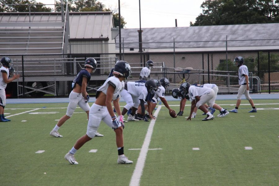 The Football team prepares to scrimmage during a practice at Poly.