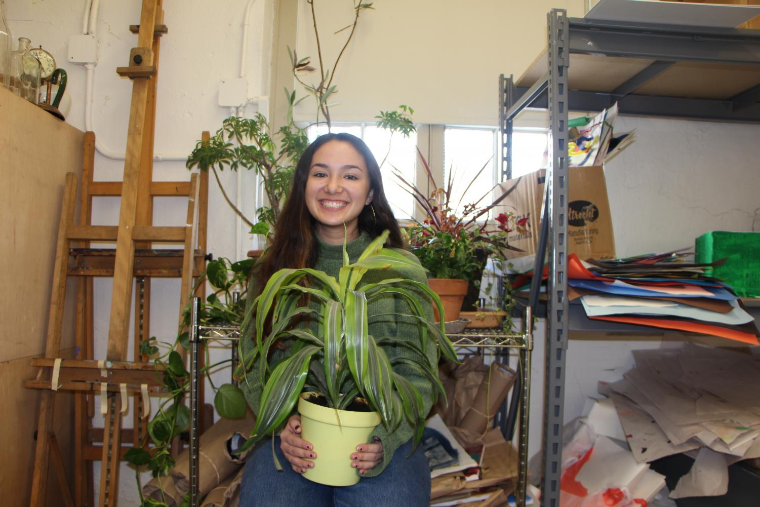A portrait of Olivia Hurley holding a potted plant.