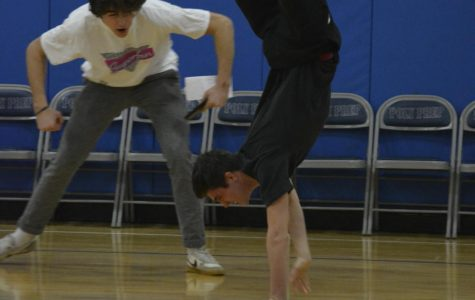 Two senior students next to one another, with one doing a handstand