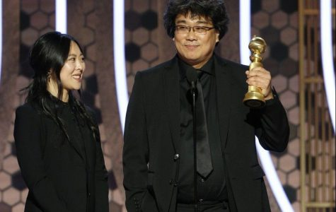 Bong Joon Ho standing on stage with female interpreter to left.