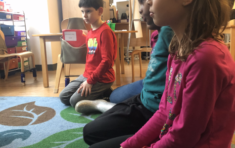 A group of elementary students kneeling on a carpet.