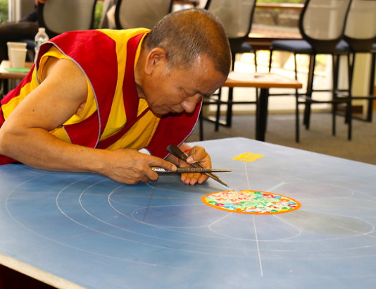 Lama Tenzin while creating the mandala in the library